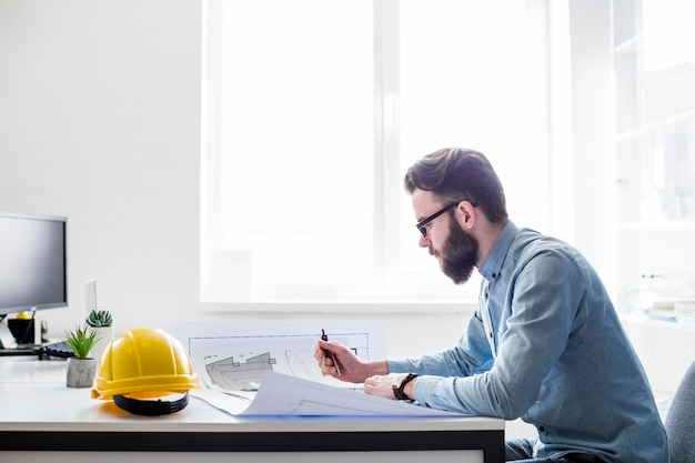 Creative engineer working on construction blueprint at workplace