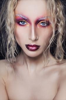 創造的なファッションと美容のクローズアップの肖像画。若いきれいな女性に創造的なメイクアップ