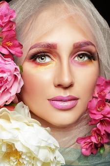 꽃 화장을 한 아름다운 젊은 여성의 창의적인 패션 뷰티 초상화