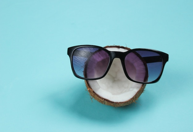 Creative fashion concept. coconut half with sunglasses on blue background