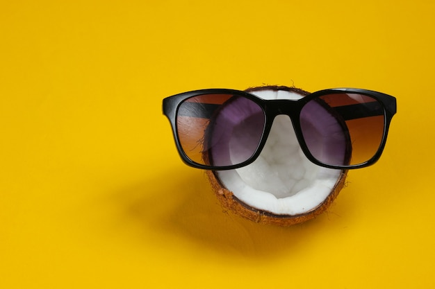 Creative fashion concept. coconut half with sunglasses on yellow background
