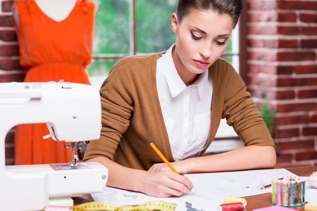 Creative fashion designer. beautiful young woman drawing fashion sketch while sitting at her working place