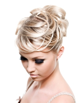 Acconciatura di moda creativa sui lunghi capelli biondi femminili