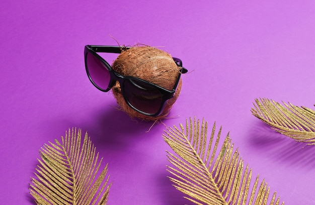 Creative fashion still life. coconut with sunglasses with golden palm leaves on purple background