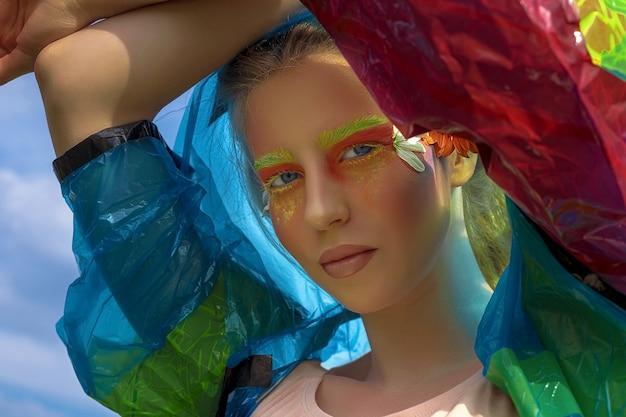 하늘을 배경으로 파란색 비옷에 긴 머리를 가진 아름 다운 젊은 여자의 창조적 인 유행 아름다움 초상화. 전문 메이크업. 확대. 신체 예술