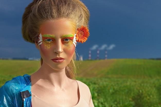 Творческий модный портрет красоты красивой молодой женщины с длинными волосами в синем плаще против неба. профессиональный макияж. крупный план. боди-арт