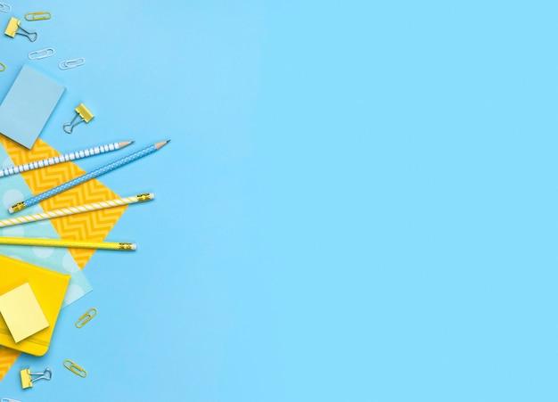 노란색 및 파란색 소모품이 포함 된 창의적이고 세련된 미니멀리즘, 학교 또는 사무실 작업 공간