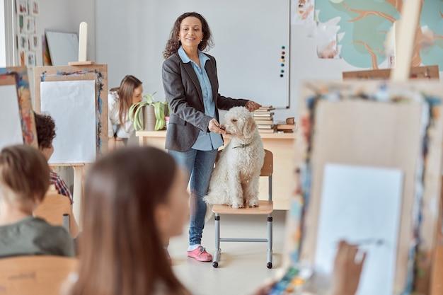 創造的な女性のアフリカの混血の教師は、学校でのグループレッスンで子供たちを描くために犬を示しています