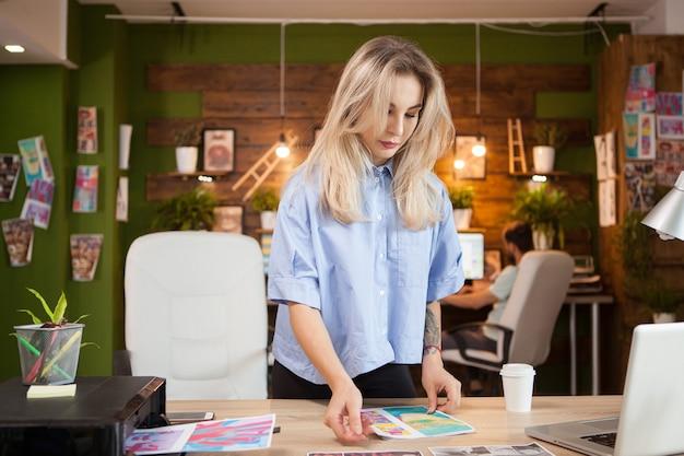 クリエイティブなオフィスで新しい服のラインのパターンをチェックするクリエイティブな女性デザイナー。