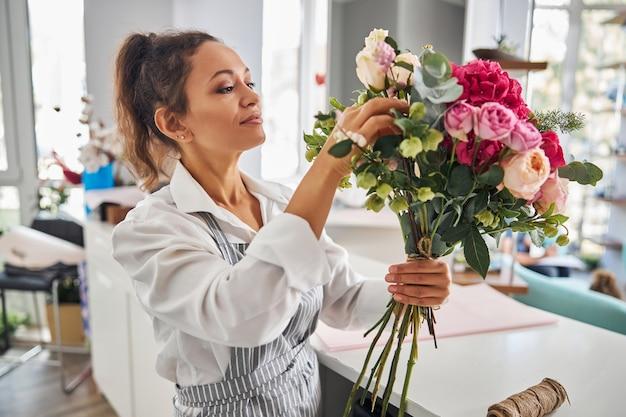 Креативный флорист-женщина восхищается созданным ею букетом