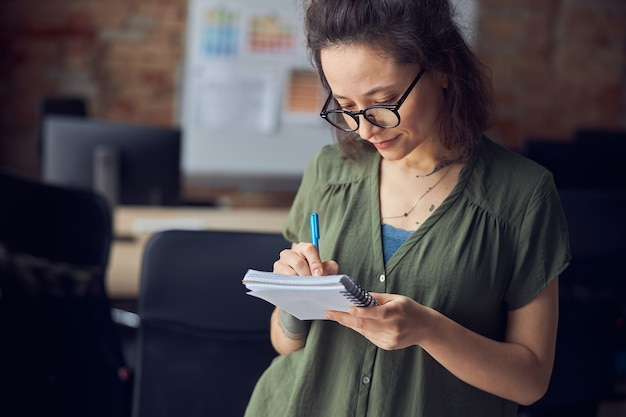 창의적인 여성 인테리어 디자이너나 안경을 쓴 건축가가 노트북 생각에 메모를 하고 있다