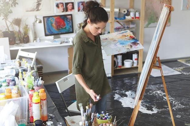 クリエイティブな女性がワークショップに立っているイーゼルにブラシのストロークを作り、さまざまなカラフルなオイルに囲まれています。水彩画とペイントブラシを使用してアートスタジオで絵を描く才能のある画家。
