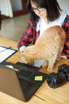 Creative female photographer with cute cat, using graphic drawing tablet and stylus pen, working at desk and retouch photo on tablet computer, retoucher workplace in photo studio home office with pet
