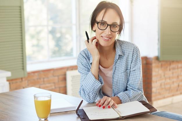 창의적인 여성 노동자가 집에 있고 메모를 쓰고 일정을 계획하고 카메라를 바라 봅니다. 여성 프리랜서는 원격으로 일하고 부엌에 앉아 있습니다.