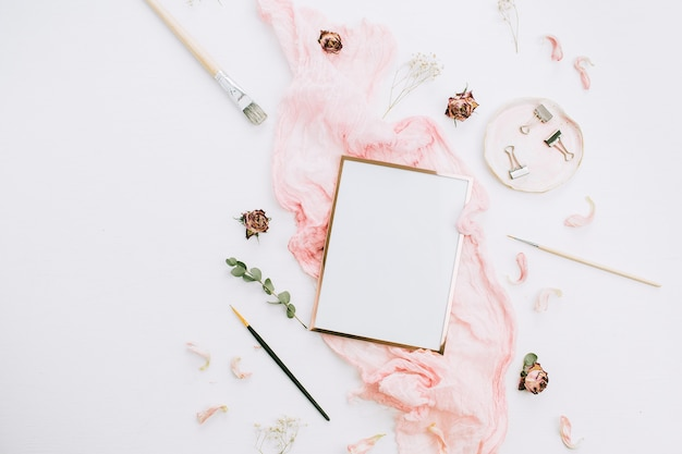 Creative festive composition with photo frame mock up, pink blanket, flowers, eucalyptus branches and brushes on white background. flat lay, top view