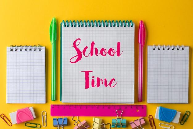 창의적인 플랫은 복사 공간, 텍스트 또는 디자인용 템플릿이 있는 밝은 노란색 종이 배경에 메모장을 사용하여 학교 개념으로 돌아갑니다. 화려한 배경에 화려한 학교 편지지