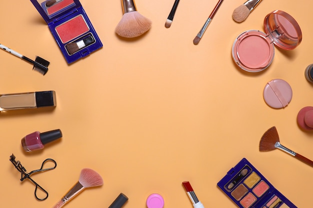Creative flat lay composition of make up set with copy space in center