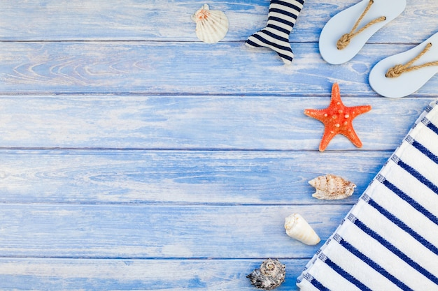 Creative flat lay concept of summer travel vacations. top view of towel flip flops seashells and starfish on pastel blue wooden planks background with copy space in rustic style frame template text