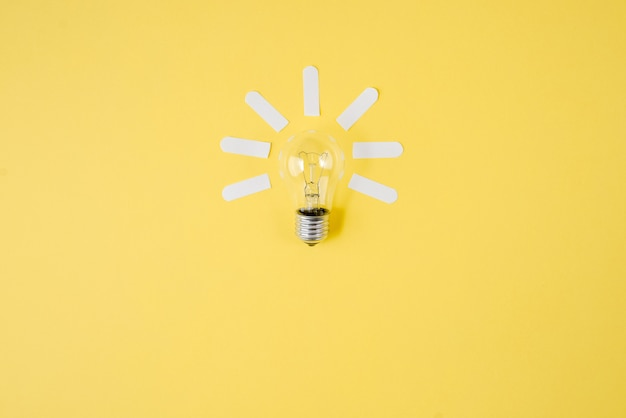 Creative flat lay concept top view of light bulb on yellow color paper background.