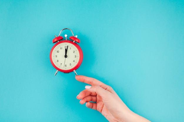 최소한의 스타일, 텍스트 템플릿 복사 공간 밝은 파란색 청록색 색 종이 배경에 빨간색 빈티지 알람 시계를 들고 여자 손의 창조적 인 평면 누워 개념 평면도