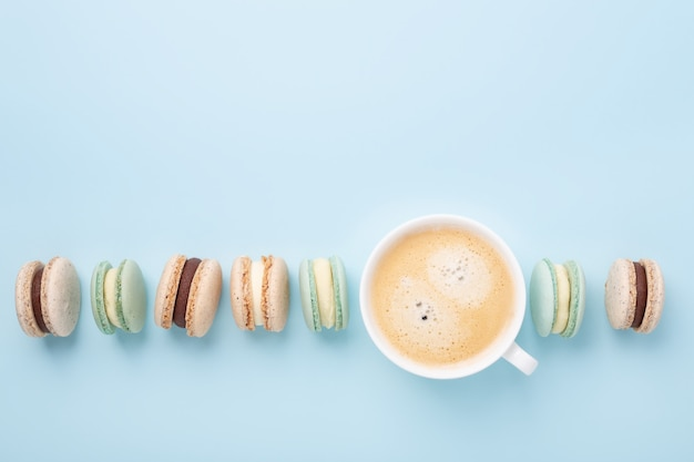 Creative flat lay. cup of coffee, various macarons on blue background. copy space for your text - image