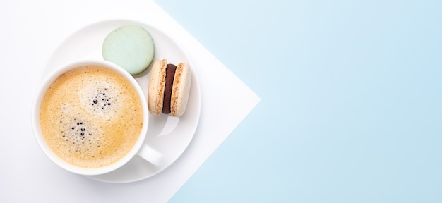 Creative flat lay. cup of coffee, various macarons on blue background. long horizontal banner - image