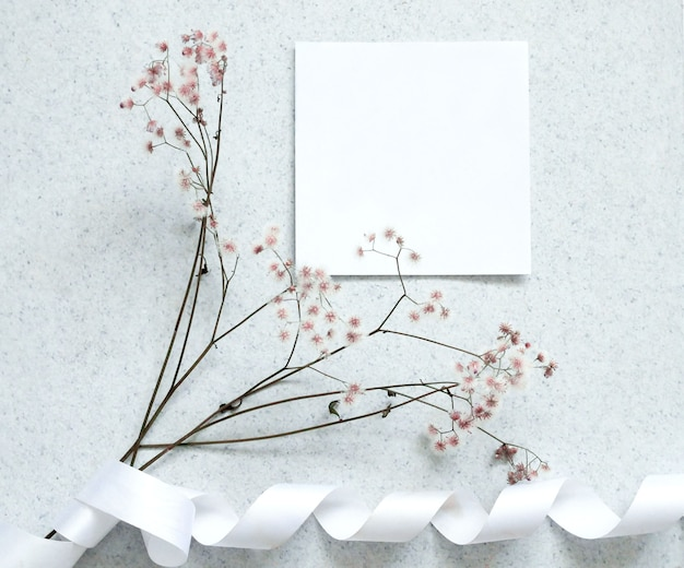 Creative flat lay design of card note with flower.