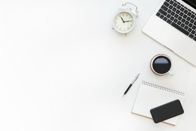 ノートパソコン、目覚まし時計、空白のノート、スマートフォン、文房具をコピースペースの背景に持つ、ワークスペースデスクのクリエイティブなフラットレイアウトデザイン