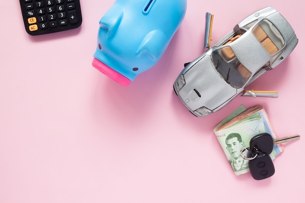 Creative flat lay of finance or car loan concept with thai banknotes on pink background