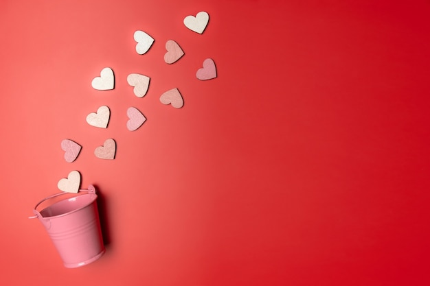 Creative flat lay of heart shape objects on bright red background falling from pink bucket. love concept