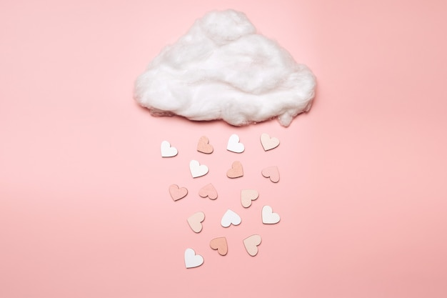 Creative flat lay of heart shape objects falling from the cloud on pastel background. love concept