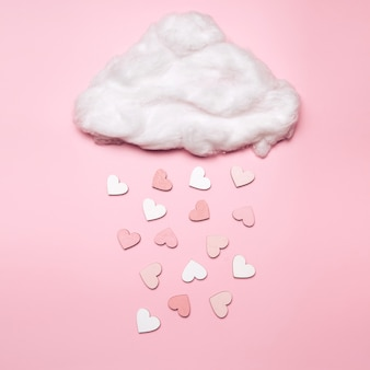 Creative flat lay of heart shape objects falling from the cloud on pastel space. love concept
