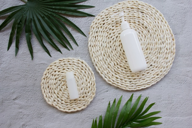 Creative flat lay of lotion and cream bottle mock up with green leaves on wicker pad