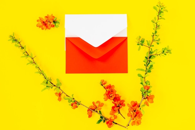 最小限のスタイルのコピースペース、レタリング、テキスト、またはデザインのテンプレートを使用して、黄色の背景にブランエンベロープフレームモックアップとマルメロの木の花びらのクリエイティブなフラットレイ。