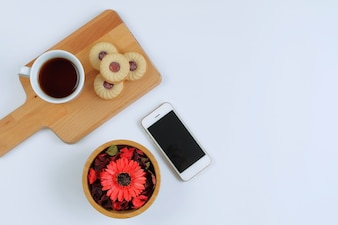 Creative flat lay of coffee, cookies, red flowers, and phone on white background with copy space