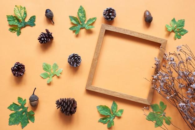 Творческий плоский лист листьев растений и сосновые шишки с деревянной рамой