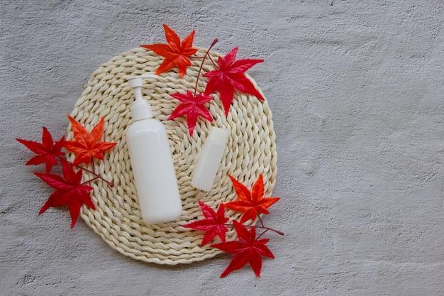 Креативная плоская пластиковая бутылка с кленовыми листьями на плетеной площадке