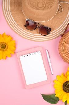 Креативная плоская планировка рабочего стола, блокнота и подсолнечника на розовом фоне