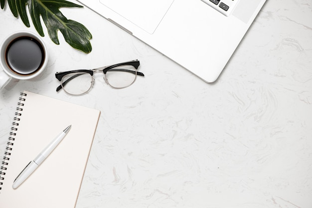 Творческая плоская планировка рабочего стола. офисный стол с ноутбуком, кофейной чашкой и белой клавиатурой, вид сверху
