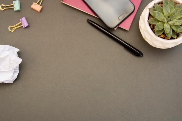 노트북, 스마트 폰, papper, 즙이 많은 식물이있는 작업 공간 책상의 창조적 인 평평한 누워. 회색 배경. 공간을 복사하십시오. 여성 작업대.
