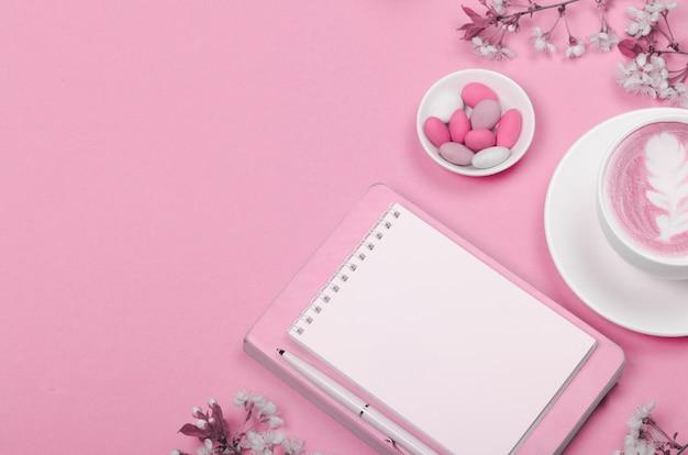 분홍색 테이블에 위시리스트 및 라이프 스타일 개체에 대한 메모장이있는 작업 공간 책상의 창조적 인 평면 배치