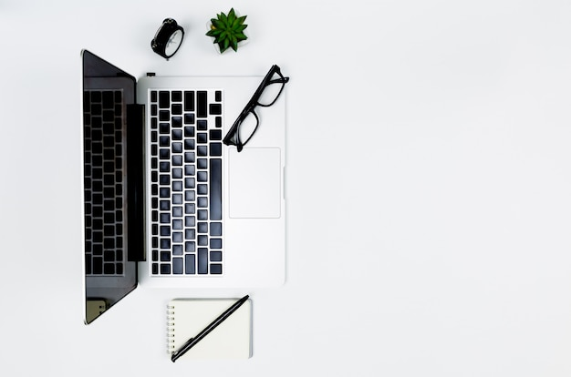 Creative flat lay photo of modern workplace with laptop, top view laptop background and copy space on white background