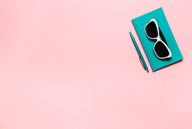 Creative flat lay photo of workspace desk with aquamarine notebook eyeglasses cactus with copy space pink background minimal style