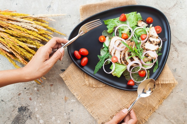 Creative flat lay of salad with grilled chicken, onions and tomatoes on black plate with woman's hands