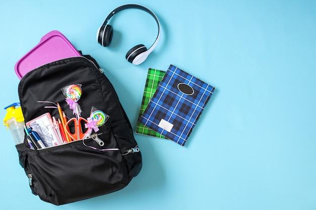 Креативная плоская школьная сумка со школьными принадлежностями на синем фоне для концепции обратно в школу