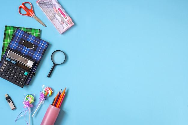 Креативные плоские школьные принадлежности на синем фоне для концепции обратно в школу