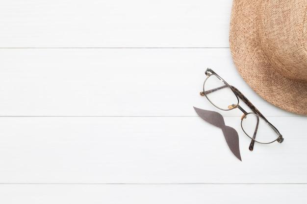 木製の背景にヒヒ、眼鏡、麦わら帽子の創造的な平らな看板、