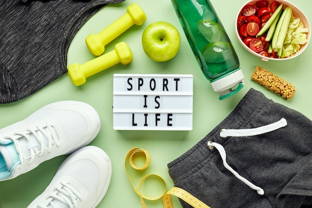 Creative flat lay of sport and fitness equipments and lightbox with sports slogan. women's white sneakers, water bottle, sportswear, dumbbells and lunchbox with healthy vegetable salad.