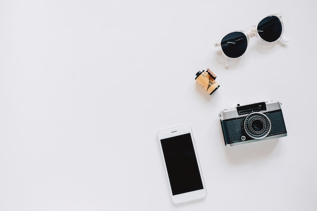 Creative flat lay style with film camera, sunglasses and smartphone on white background with copy space