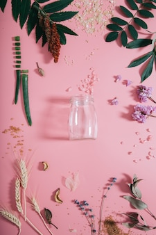 Creative flat lay top view of empty bottle on pastel millennial pink paper wall copy space.